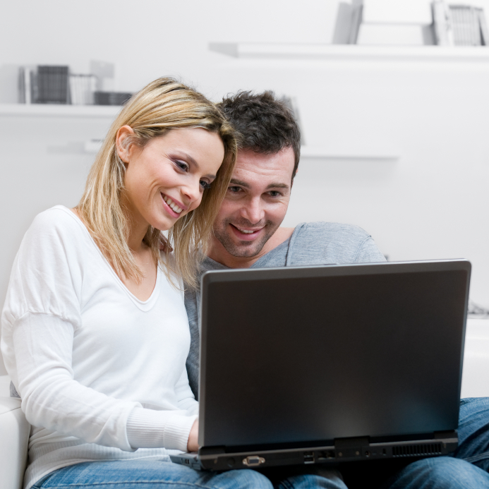 Young happy couple surfing the net with their laptop at home